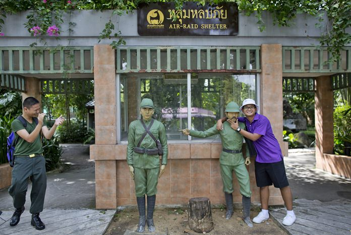 A man poses for a photo at the entrance to an old air-raid shelter, at the Dusit Zoo in Bangkok. (AP Photo/Gemunu Amarasinghe)