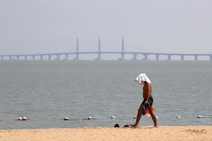 A man walks past a beach as the Zhuhai-Macau-Hong Kong Bridge looms in the background in Zhuhai in south China's Guangdong province. (AP Photo/Andy Wong)