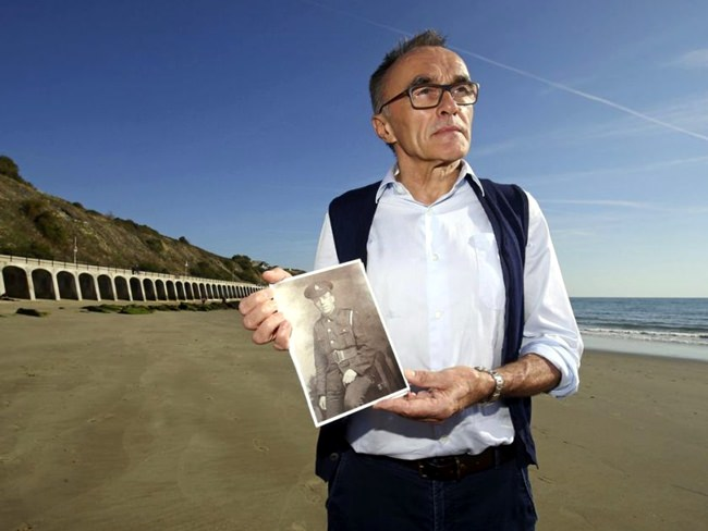 British filmmaker Danny Boyle holds a photograph of Private Walter Bleakley, who lived on the same street where Boyle went to school, as he announces plans for his Armistice Day First World War centenary commemoration, on the beach, in Folkestone, England, Friday Oct. 5. (Gareth Fuller/PAvia AP)