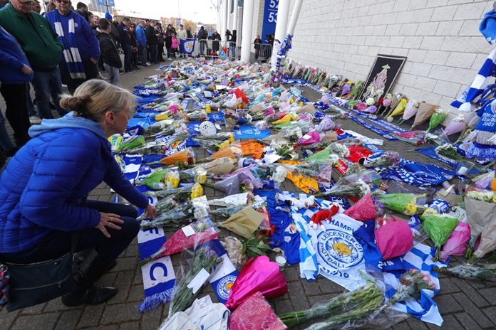 Supporters pay tribute outside Leicester City Football Club after a helicopter crashed in flames the previous day, in Leicester, England, Sunday, Oct. 28, 2018. (Aaron Chown/PA via AP)