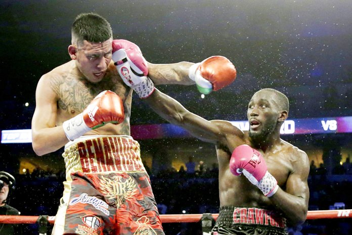 Terence Crawford, right, connects with Jose Benavidez during their WBO welterweight title boxing bout in Omaha, Neb., Saturday, Oct. 13. (AP Photo/Nati Harnik)