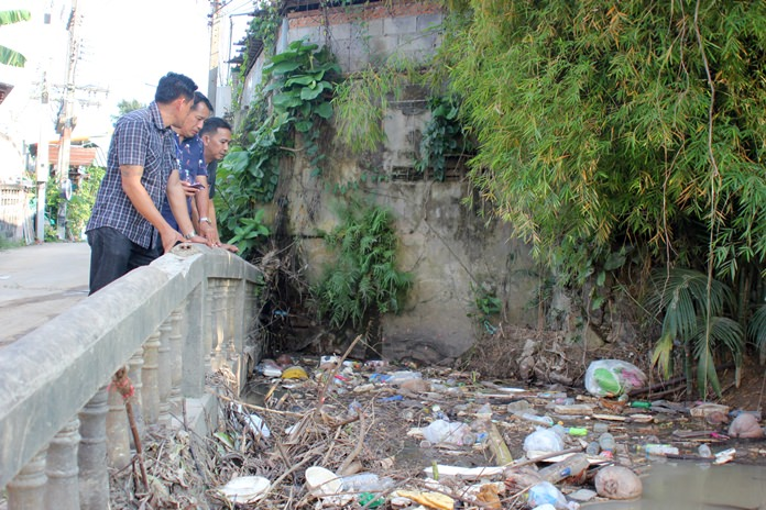 Deputy City Manager Passakorn Usomboon and Sanitation Department workers survey the Kratinglai Canal at Paisan village.