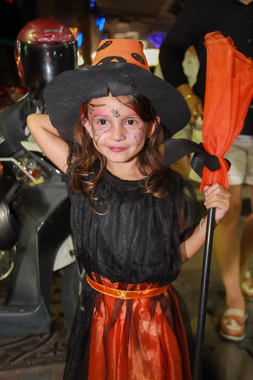 A little witch pauses for some candy before taking off on her broom.