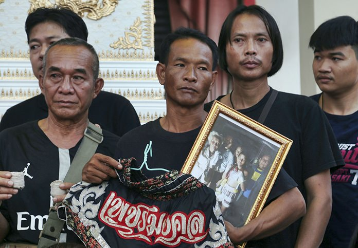 Relatives of 13-year-old Thai kickboxer Anucha Tasako hold his boxing shorts and a portrait during his funeral services in Samut Prakan province. Anucha died of a brain hemorrhage two days after he was knocked out in a bout on Nov. 10 that was his 174th match in the career he started at age 8. (AP Photo/Sakchai Lalit)