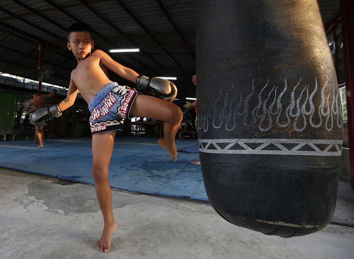 In this Wednesday, Nov. 14, 2018, photo, Thai kickboxer Chaichana Saengngern, 10-years old, practices kicks at a training camp in Bangkok. (AP Photo/Sakchai Lalit)