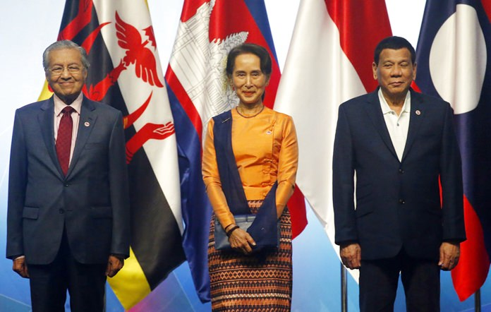 ASEAN Leaders pose for a photo during the opening ceremony for the 33rd ASEAN Summit and Related Summits Tuesday, Nov. 13, 2018, in Singapore. From left; Prime Minister Mahathir Mohamad of Malaysia, Myanmar Leader Aung San Suu Kyi and President Rodrigo Duterte of The Philippines. (AP Photo/Bullit Marquez)