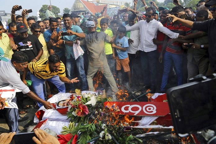 Supporters of the United National Party (UNP) and ousted Prime Minister Ranil Wickremesinghe burn coffins to represent the death of democracy during a protest against the government of disputed Prime Minister Mahinda Rajapaksa in Colombo, Sri Lanka, Thursday, Nov. 15. (AP Photo/Rukmal Gamage)