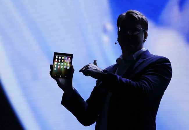 Justin Denison, SVP of Mobile Product Development, shows off the Infinity Flex Display of a folding smartphone during the keynote address of the Samsung Developer Conference Wednesday, Nov. 7, in San Francisco. (AP Photo/Eric Risberg)