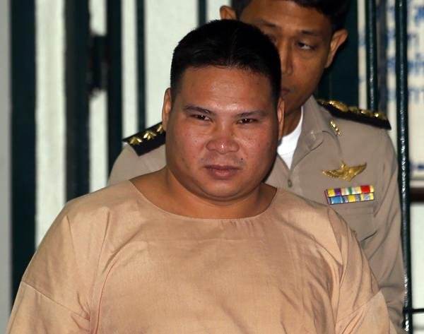 """In this Thursday, March 3, 2016, file photo, Vivat Yodprasit, the """"Popcorn Gunman,"""" is escorted by correctional officers while arriving at Criminal court in Bangkok. (AP Photo/Sakchai Lalit)"""