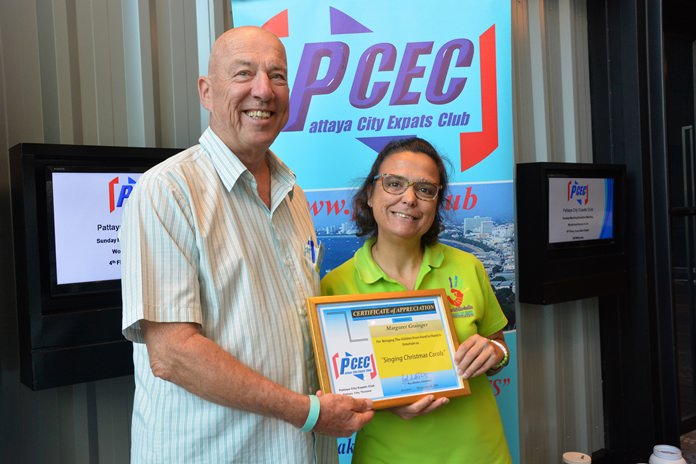 MC Roy Albiston presents Margie Grainger with the PCEC's Certificate of Appreciation for bringing some of the Hand to Hand Foundation children to entertain with an early Christmas program.
