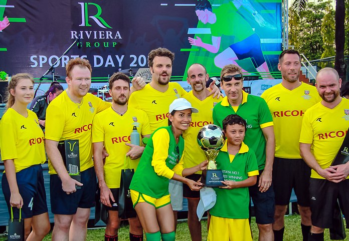 Winston and Sukanya Gale and their son Toby of the Riviera Group team (green shirts) present the football champions trophy to the victorious Regents School football squad during the Riviera Group Sports Day, November 24 at the Regents International School in Pattaya.