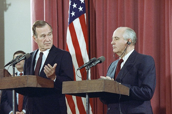 In this Oct. 29, 1991, file photo, President George H.W. Bush gestures during a joint news conference with Soviet President Mikhail Gorbachev, at the Soviet Embassy in Madrid. (AP Photo/Jerome Delay, File)