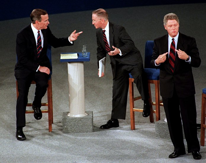In this Oct. 15, 1992, file photo, President George H.W. Bush, left, talks with independent candidate Ross Perot as Democratic candidate Bill Clinton stands aside at the end of their second presidential debate in Richmond, Va. (AP Photo/Marcy Nighswander, File)