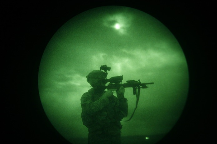 A U.S. soldier looks through the scope of his weapon during a night patrol in Mandozai, in Khost province, Afghanistan, seen through night vision equipment. About 400,000 veterans had a PTSD diagnosis in 2013, according to the Veterans Affairs health system. (AP Photo/Rafiq Maqbool)
