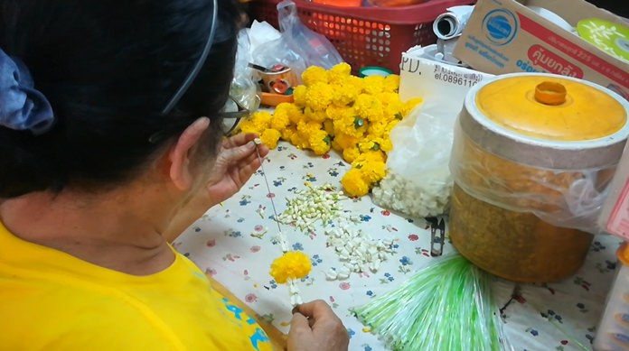 A woman lovingly and painstakingly creates a jasmine flower garland for Fathers' Day.