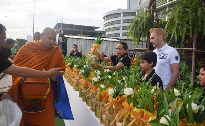 The Gale family make offerings of rice and dried foods to Buddhist monks.