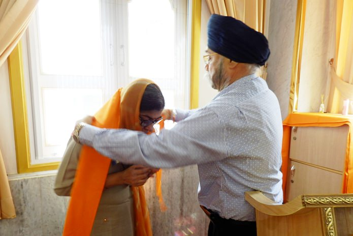 Paramjit Singh Ghogar drapes the sacred saffron shawl over Her Excellency's shoulders.