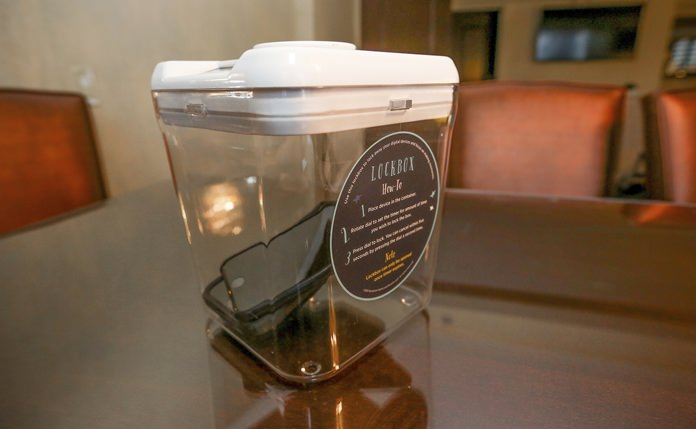This Dec. 1, 2018 photo shows a locked box holding cell phones during a digital detox visit to the Wyndham Grand Hotel in Chicago. A growing number of hotels are helping guests take a vacation from their vacation by offering incentives to guests willing to lock up their cell phones. (AP Photo/Teresa Crawford)