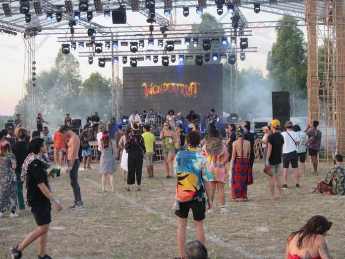 Smoke drifts across the stage as festival goers enjoy live music at the 5th Wonderfruit Festival in Pattaya.