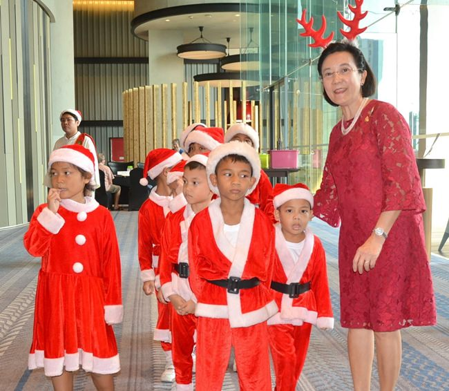 Toy Radchada from the Pattaya Orphanage leads some of the younger choir members to their assembly area prior to the start of the PCEC's Christmas program.