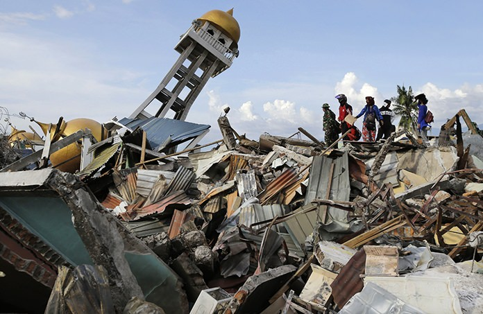 Rescuers and villagers wait for news for their missing loved ones as recovery efforts continue after liquefaction hit the neighborhood of Balaroa in Palu, Central Sulawesi, Indonesia, on Oct. 6, 2018. (AP Photo/Aaron Favila)