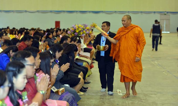 A revered monk blesses with holy water more than 4,000 area school teachers and educational administrators at the Teacher's Day celebration inside the National Indoor Sports Area.
