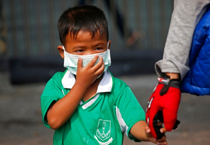 A young boy wears a protective mask for the high levels of air pollution as he's picked up from school in Bangkok, Wednesday, Jan. 30. (AP Photo/Sakchai Lalit)