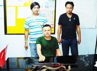 Worawut Langlorm (seated) points to the AK-47 he tried to sell over the Internet.