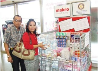 A benevolent couple places packets of foodstuffs in the collection area at Makro Pattaya Branch, for distribution to victims of the floods in the country.