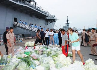 Officers, crew and civilians begin loading supplies headed for the flood stricken south.