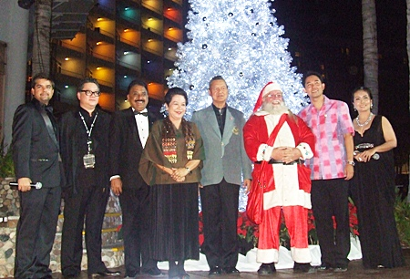 (l-r) Tony Malhotra, Jorge Carlos Smith, Peter Malhotra, Khunying Busyarat and Gen. Kanit Permsub, Santa Claus, Mayor Itthiphol Kunplome and Rungratree Thongsai gather for a photo in front of the lit up Christmas tree.