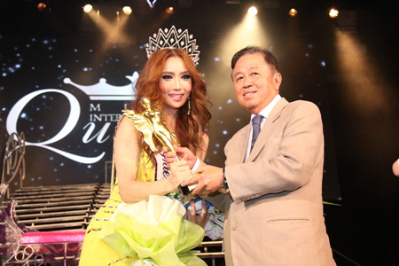 South Korean Minnie Han receives the Miss International Queen 2010 trophy from Sutham Phanthusak, managing director of the Tiffany Show Company Pattaya.