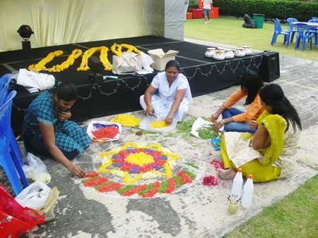 Parents make rangoli.