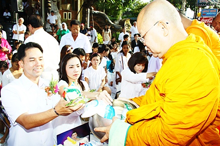 Mayor Itthipol Khumplome and his wife Rachada Chatikavanij enjoy making merit together by giving alms to the Buddhist monks.