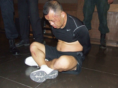 Beaten and bruised, Jun Sang Ho is handcuffed whilst awaiting being taken to the police station for processing.
