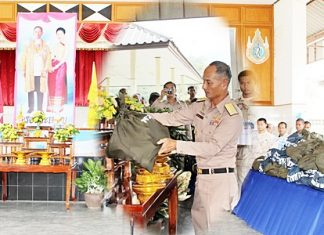 In front a portrait of Their Majesties the King and Queen, Rear Adm. Chainarong Kaowiset, Chief of Staff in Navy Region 1, presides over ceremonies to begin distribution of 400 bags of emergency supplies to flood victims in Chumphon.