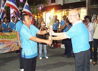 Wattana Chantanawaranon, Deputy Mayor of Pattaya City, receives the auspicious National Games torch from a representative of the Takhiantia Municipality on Monday, December 7 at Bali Hai Pier, Pattaya.