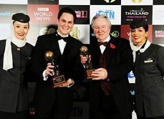"""Peter Baumgartner (left), Etihad's chief commercial officer, celebrates winning the title for """"World's Leading Airline"""" and """"World's Leading First Class"""" airline at the World Travel Awards, with Graham Cooke (right), president and founder, World Travel Awards, and Etihad cabin crew members."""