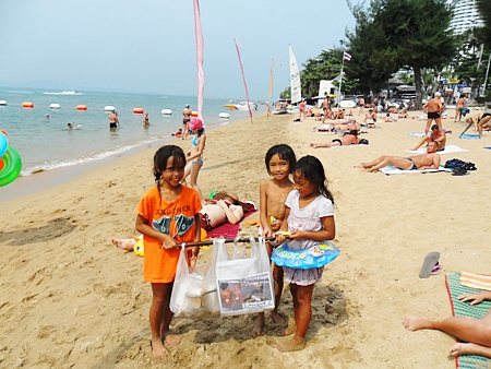 Three young beachcombers help to keep the place clean.
