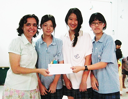 Margaret Grainger receives an 80,000 baht donation to the Hand to Hand center from ISE students.