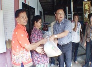 Deputy Mayor Wutisak Rermkitkarn, centre right, hands over relief supplies to Naklua resident Viang Saengthong, left, after the latter's house was badly damaged during a Feb. 15 rainstorm.