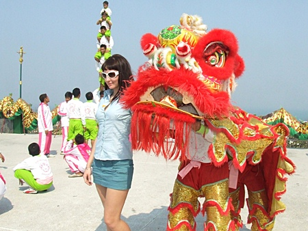This lovely visitor poses for a commemorative photo with one of the lion dancers.