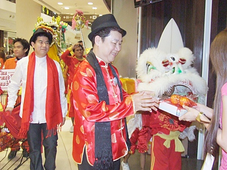 Saran Tantichamnan, GM of Central Festival Pattaya Beach, and his dragon and lion dance team visit shopkeepers to wish them a Happy New Year.