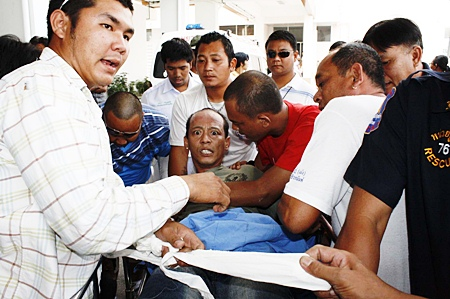After subduing an irate Suparit from the streets, rescue workers return him to the hospital for treatment.