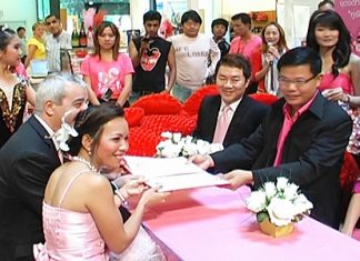 British national Gary Howard, 52, and new bride Kwanruen Laklaem, 32, seated left, tie the knot on Valentine's Day in front of Banglamung District officials at Central Festival Pattaya Beach.