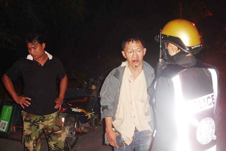 A badly beaten Sithichok Pipatsin explains to a police officer how he was attacked by two assailants.