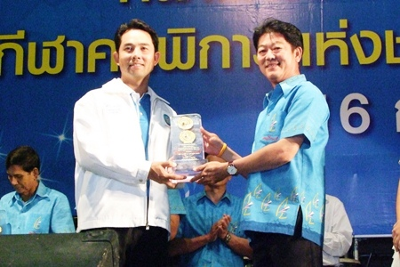 Chonburi Governor Wichit Chatpaisit, right, presents a token of thanks to Pattaya Mayor Ittiphol Khumplome, left, to recognize the city's help in hosting the 39th National Games and National Disabled Games in December and January.
