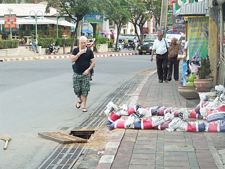 The offending hole without its drainage cover poses a hazard to pedestrians and motorists alike.