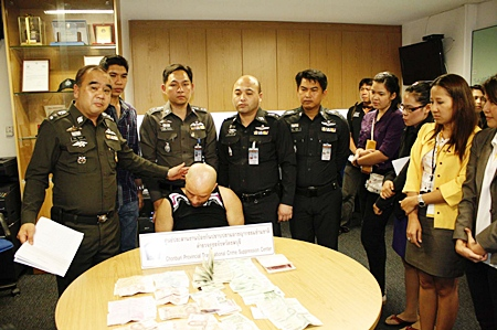 Paul Adrain Trica sits head bowed at Pattaya Police Station following his arrests on charges of theft from currency exchange booths.