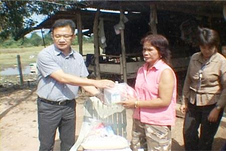 Deputy Mayor Wutisak Rermkitkarn, left, hands over some emergency living provisions to distraught homeowner Noi Pumart.